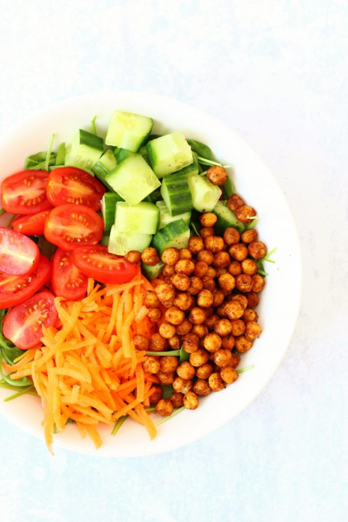 Bowl of salad including roasted chickpeas, cucumber, tomatoes and grated carrot