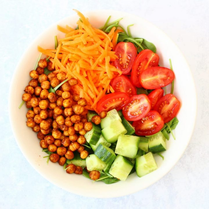 Bowl of roast chickpea salad with cucumber, tomatoes, carrot and rocket as well as roasted chickpeas