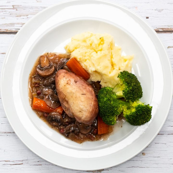 Plate of coq au vin with mashed potatoes and broccoli