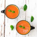 two bowls of tomato soup topped with basil