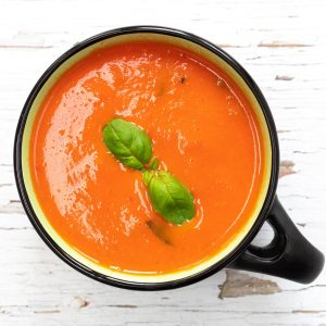 classic tomato soup in a bowl with basil on top