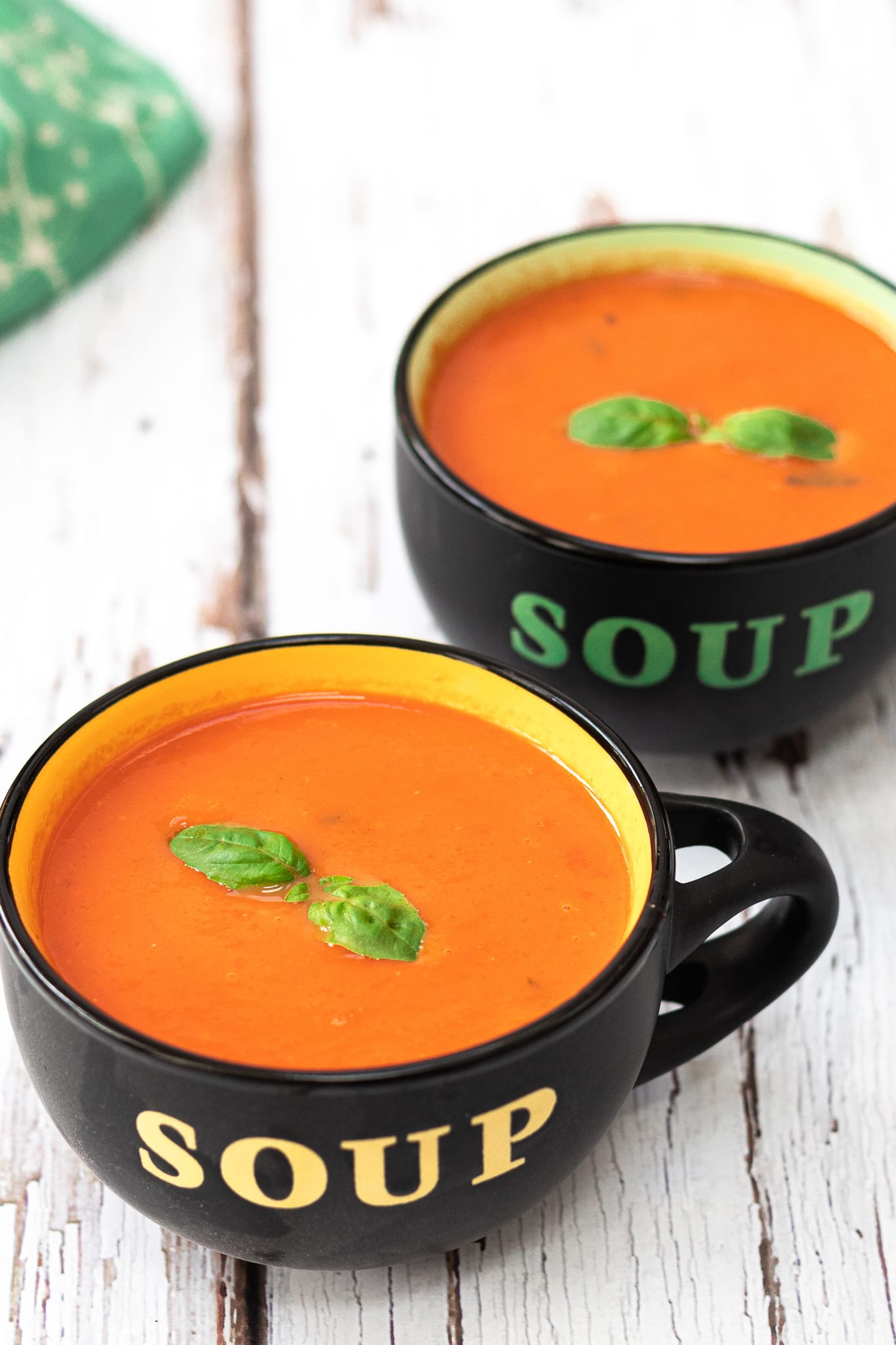 two bowls of tomato soup with basil on top