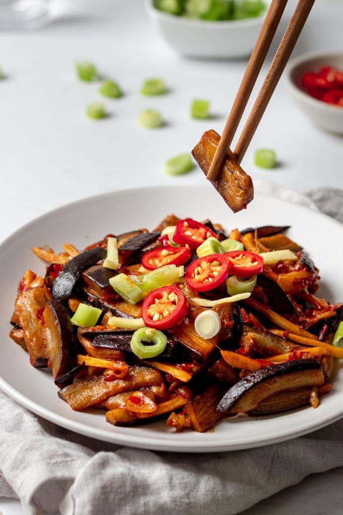 chopsticks holding a piece of aubergine in chilli bean paste