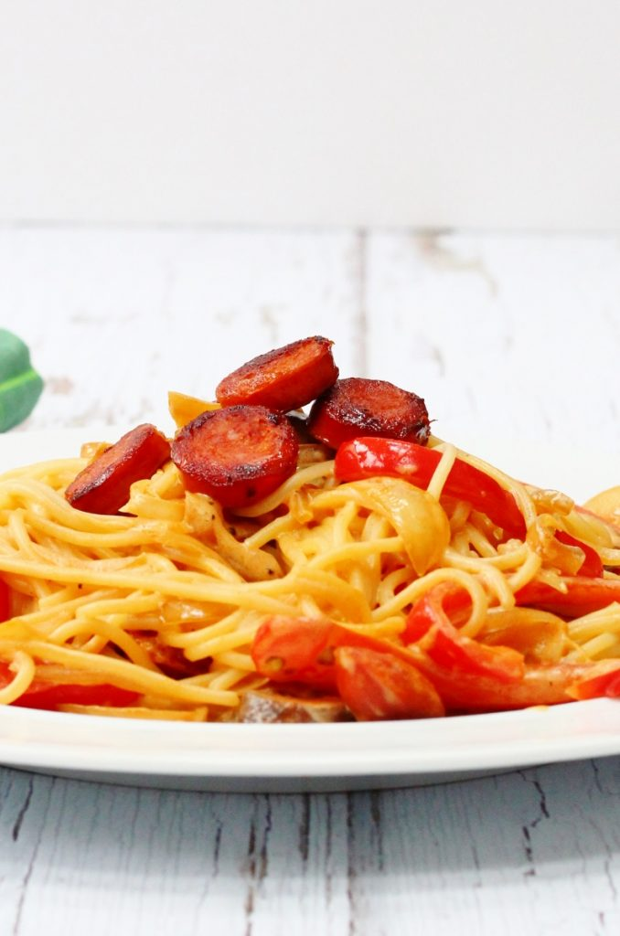 plate of spaghetti with a creamy red pepper mushroom sauce and crispy pieces of chorizo