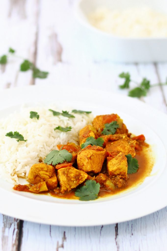 Red Goan chicken curry on a plate with rice in the background