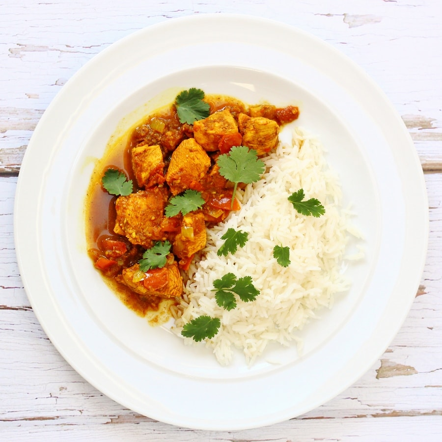 Rd Goan chicken curry with rice and coriander leaves