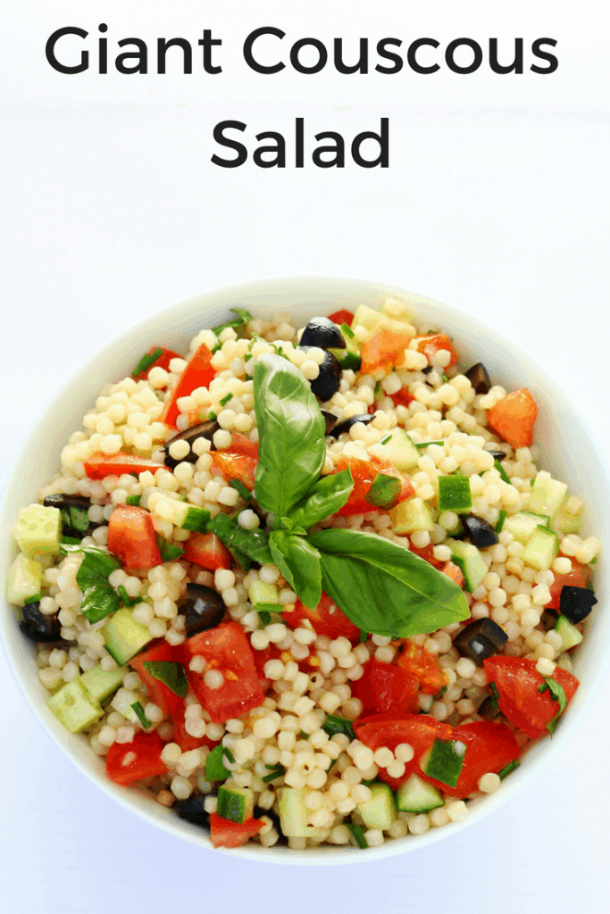 bowl of giant couscous salad topped with basil leaves