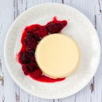 Vanilla panna cotta on a plate with a red berry sauce