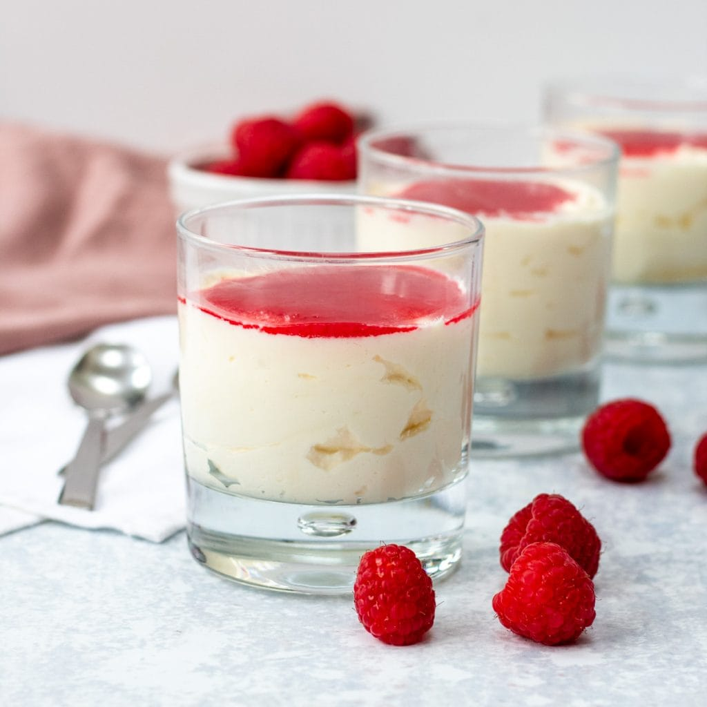 Three glasses with white chocolate mousse and raspberry sauce
