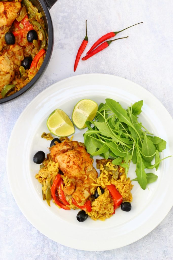 Pot and plate of Puerto rican chicken dish which is chicken cooked in spicy rice