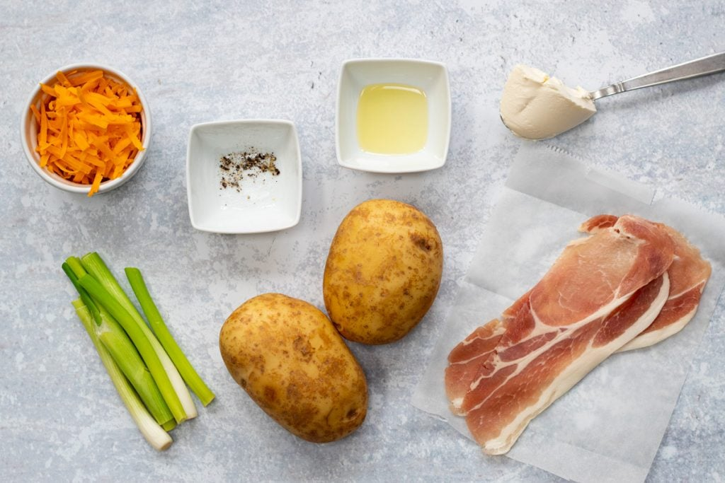 Ingredients for stuffed potato skins: Baking potatoes, bacon, cheese, cream cheese, spring onions, oil, salt and pepper