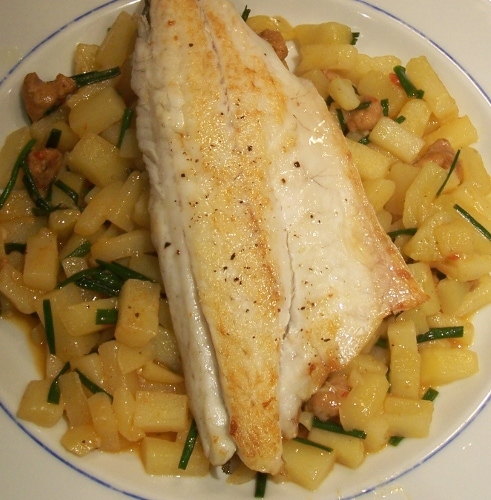 plate of chorizo and potato risotto with sea bass on top