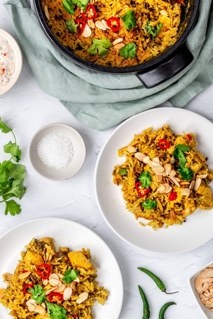 flatlay of chicken biryani with pot and plates