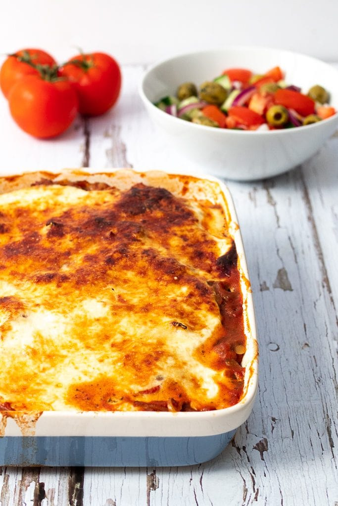 Dish of vegetarian Moussaka with salad and tomatoes in the background
