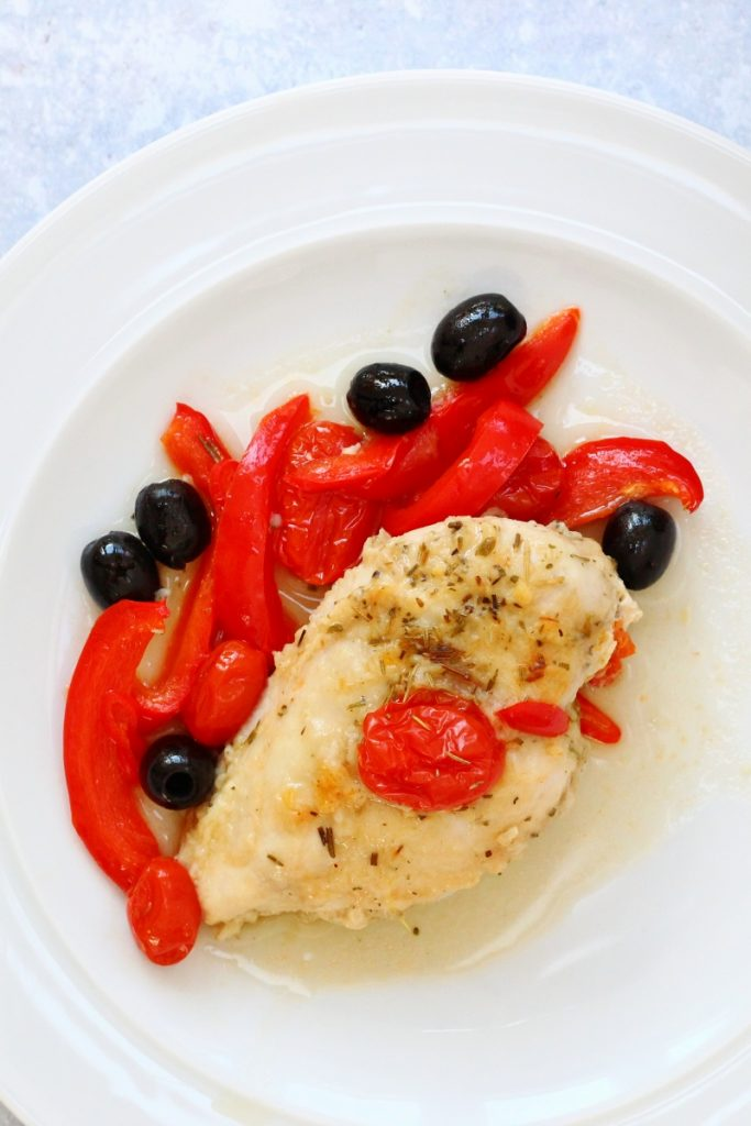 Baked Italian chicken iwth peppers, tomotoes and olives on a plate