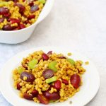 Curried pearl barley salad on a plate with a serving bowl in the background