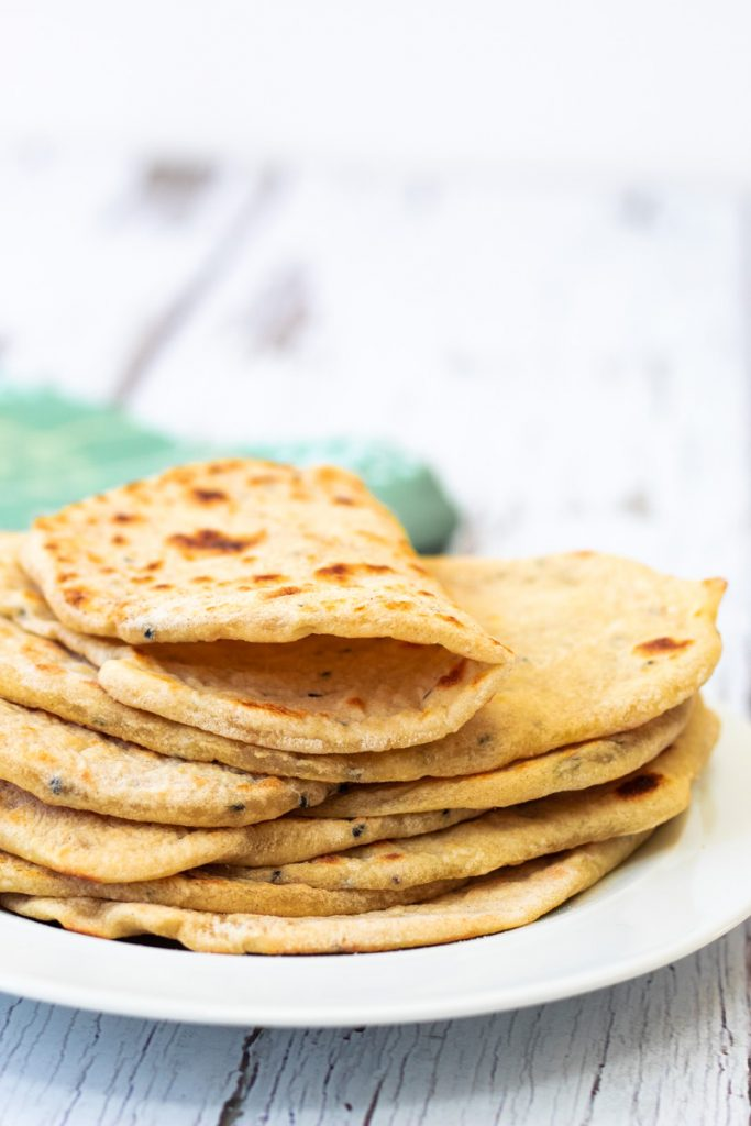nigella seed flatbreads in a stack with one folded in half