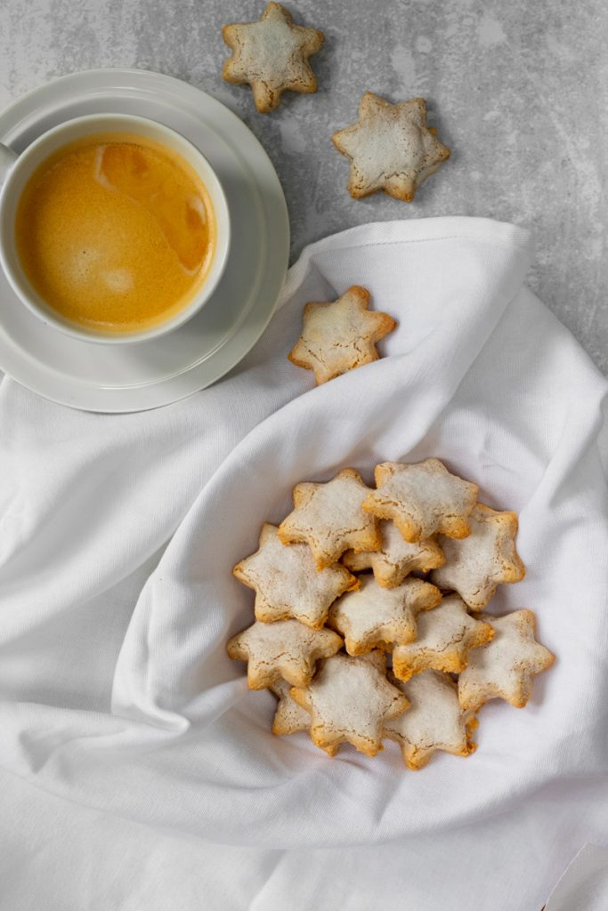 flatlay of cinnamon star biscuits with cup of coffee