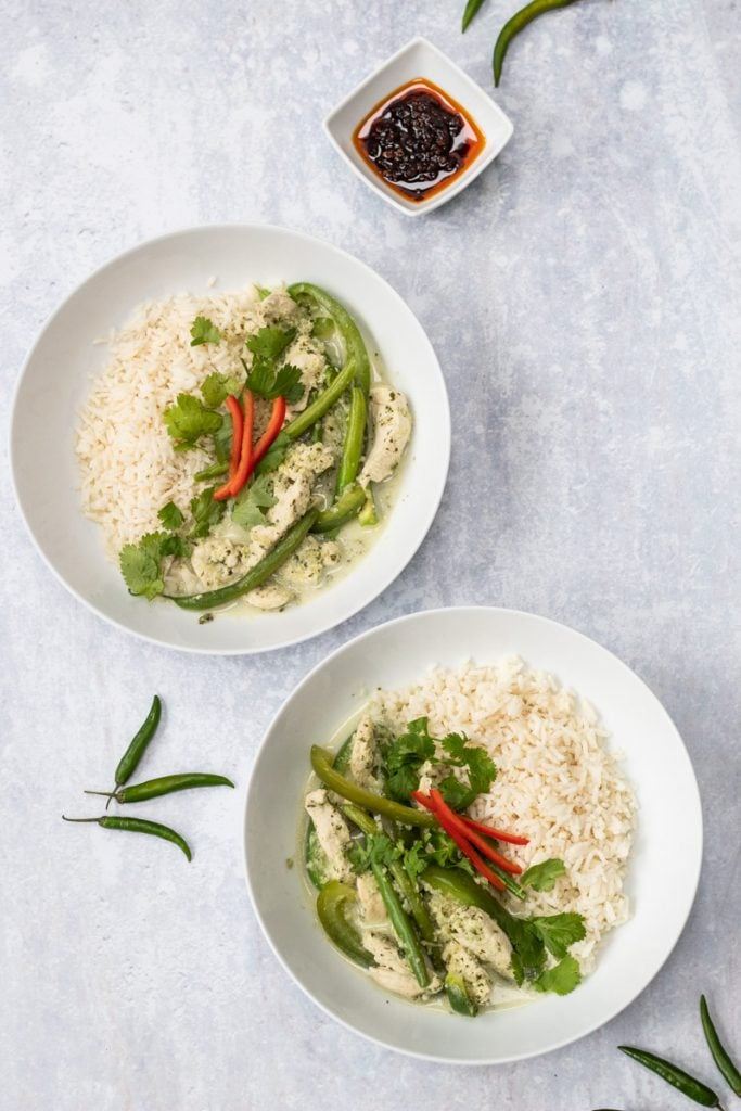 Two bowls of Thai green curry and chilli sauce
