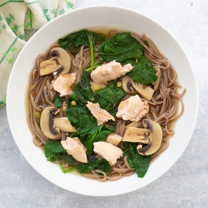 bowl of salmon miso soup with soba noodles, spinach and mushrooms