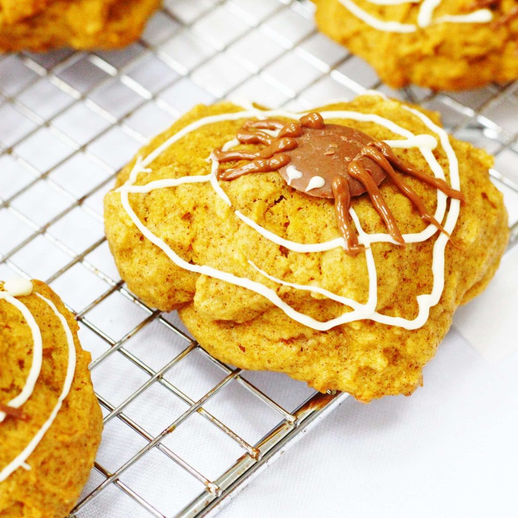 Spiced pumpkin cookies decorated with chocolate webs and spiders for Halloween