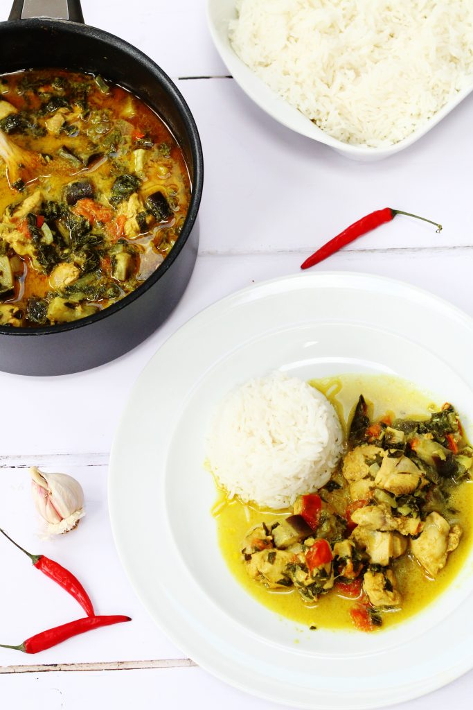 chicken and callaloo curry on a plate with rice