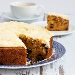 Carrot cake with a slice in the background and cup of coffee