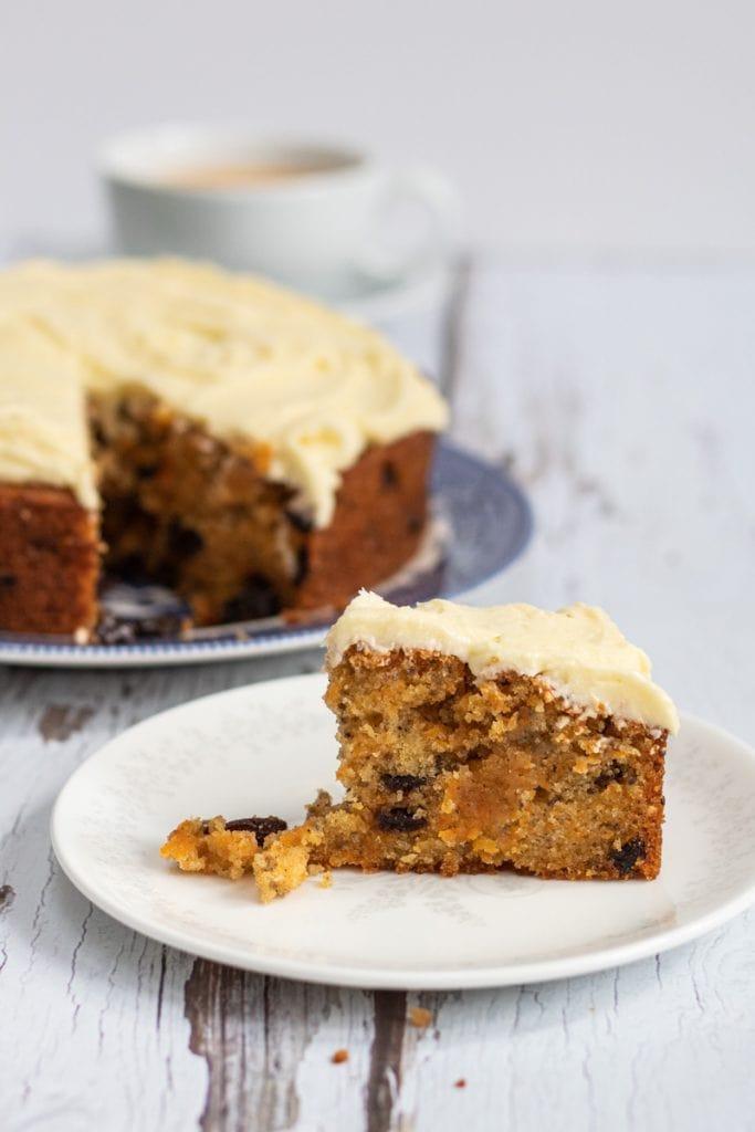 vegan carrot cake slice with cake in background