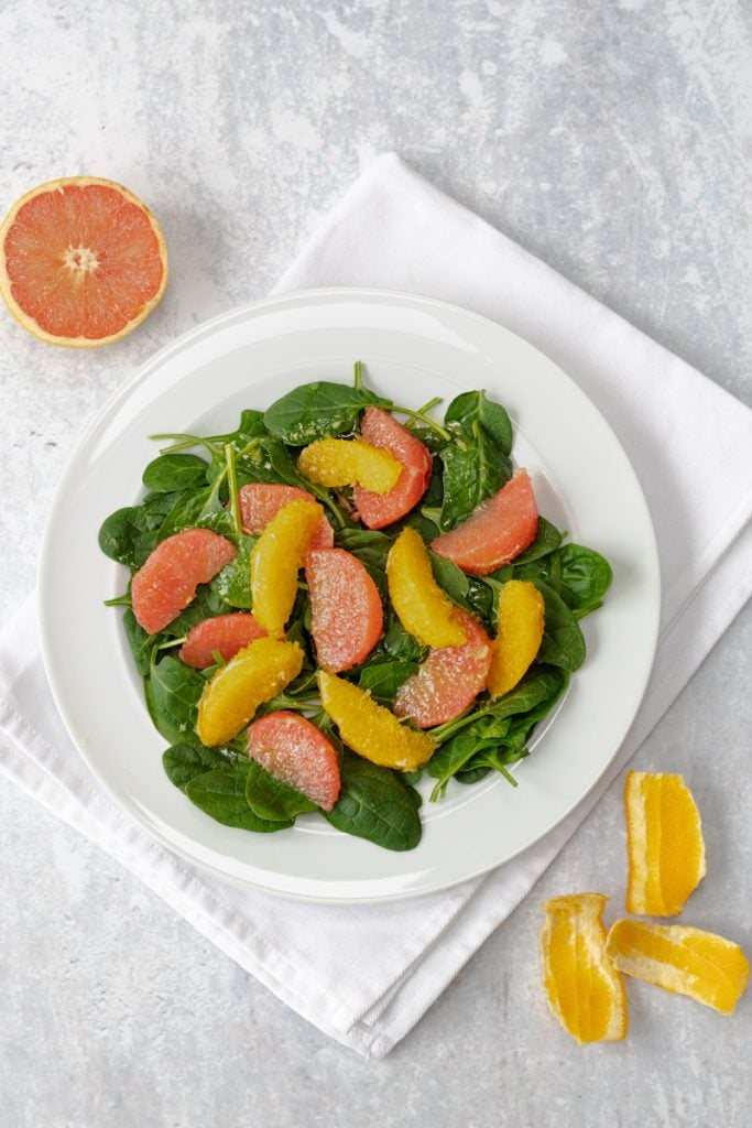 Plate of salad with spinach leaves and citrus fruit