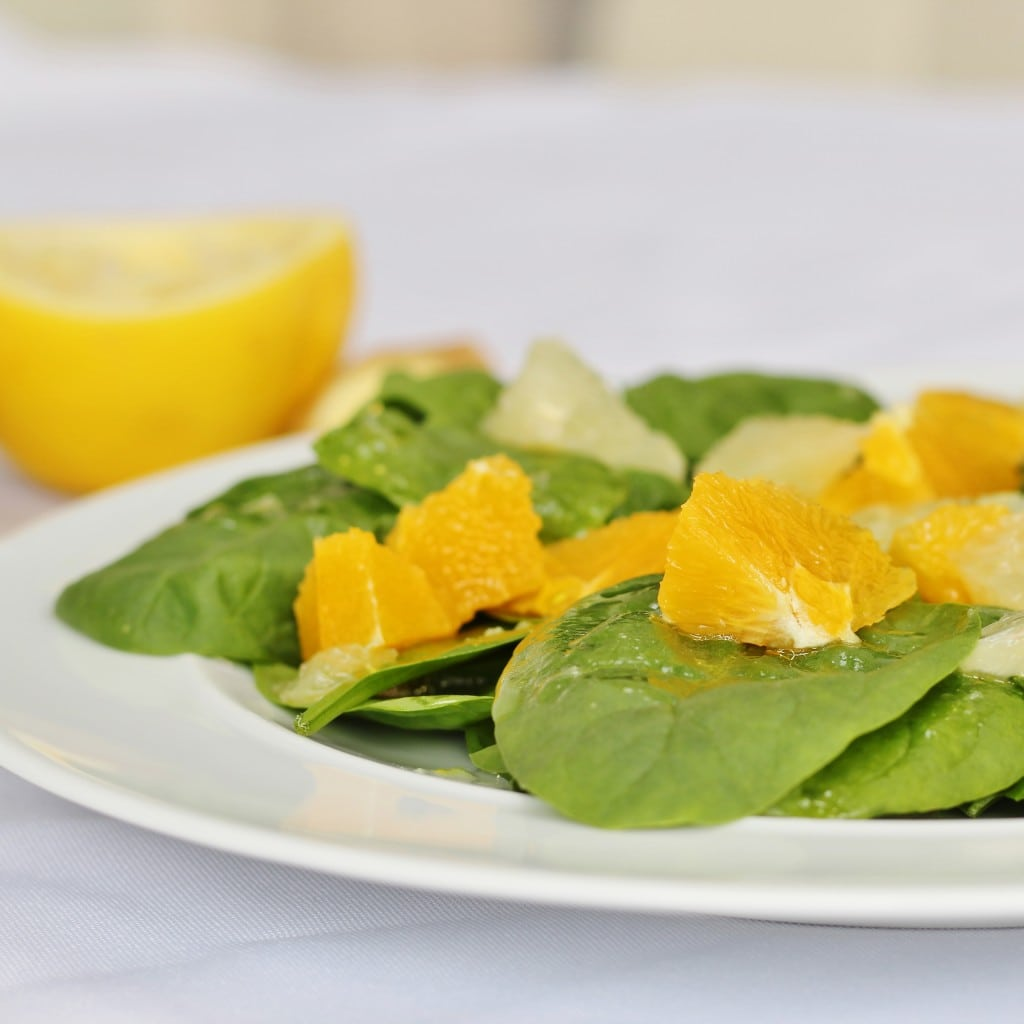 spinach citrus salad with grapefruit in the background