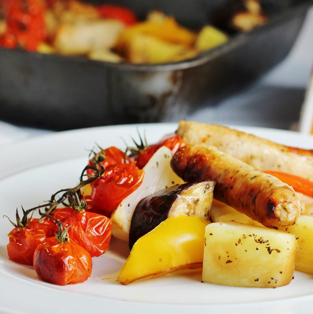 Close up of sausage tray bake on a plate showing sausages, tomatoes, potatoes, aubergine and peppers