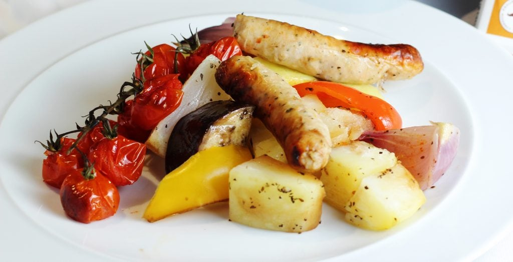 White plate with sausages, potatoes, tomatoes and roasted vegetables
