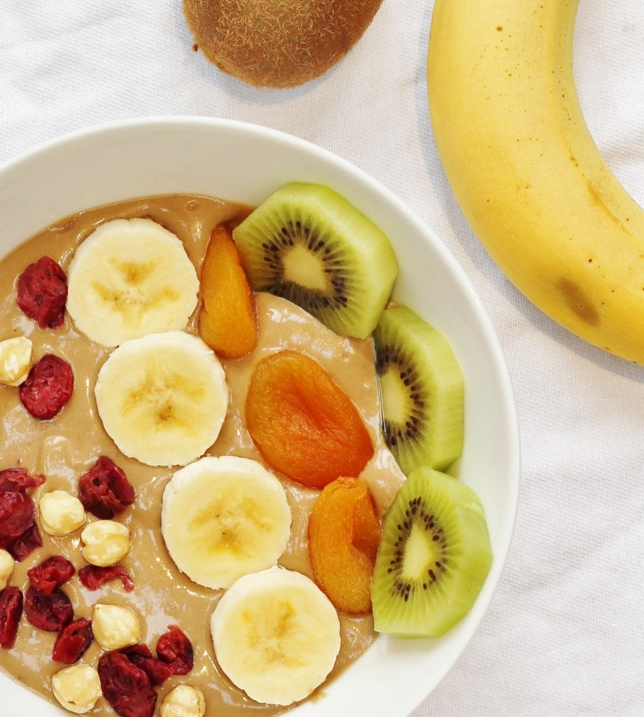 Healthy Nutella smoothie bowl with banana and avocado topped with banana, kiwi fruit, dried apricots, cranberries and hazelnuts