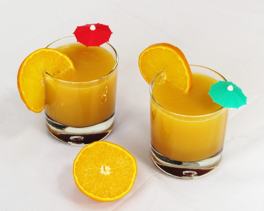 Two glasses of orange and pomegranate molasses mocktail