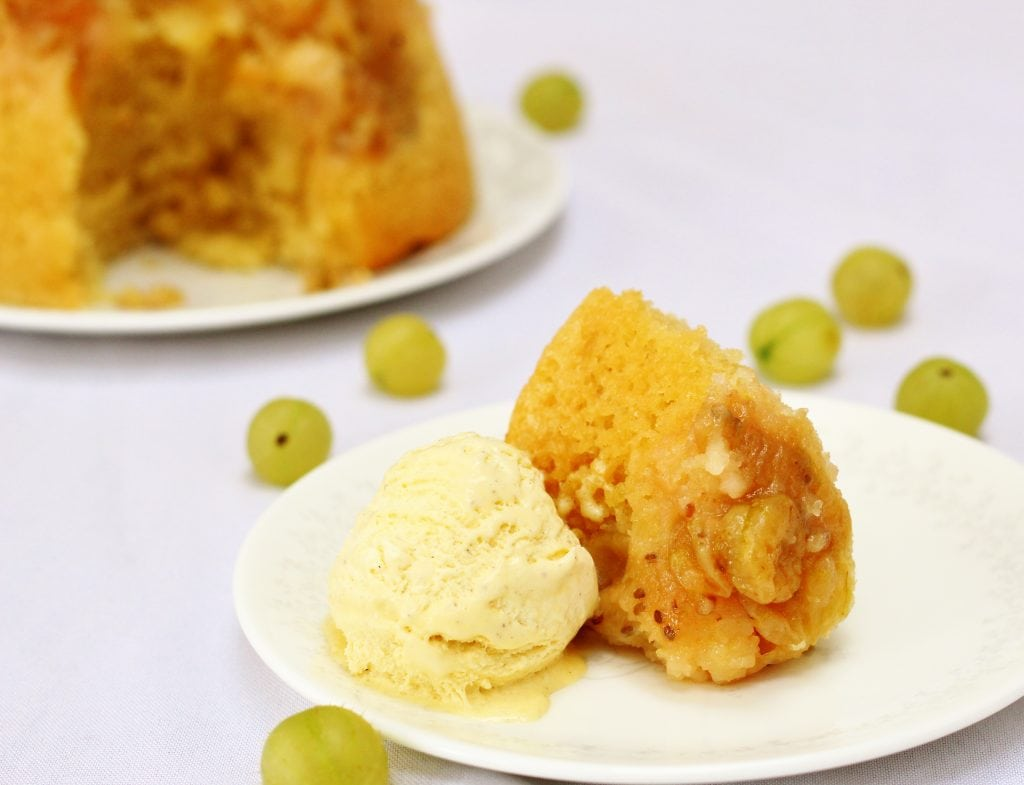 Plate of slow cooker gooseberry steamed sponge pudding with ice cream
