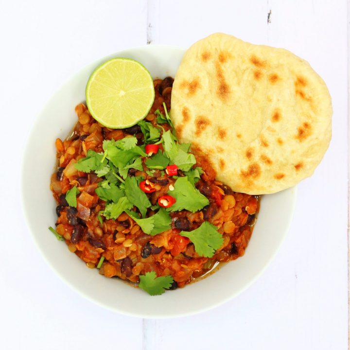vegan lentil chilli in a bowl with a flatbread