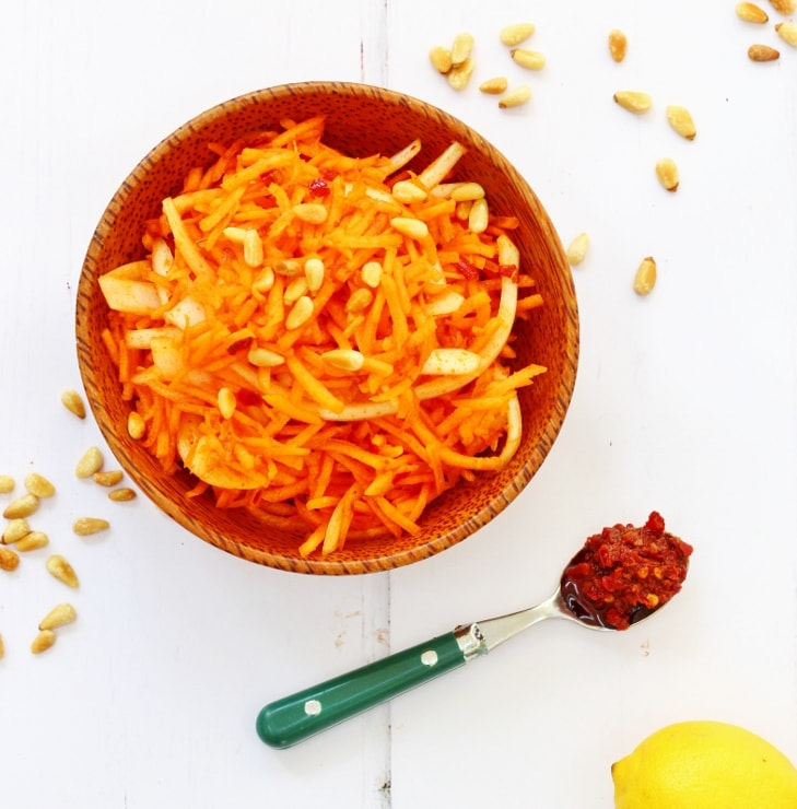 harissa carrot salad in a brown bowl on a white background with a spoonful of harissa next to it