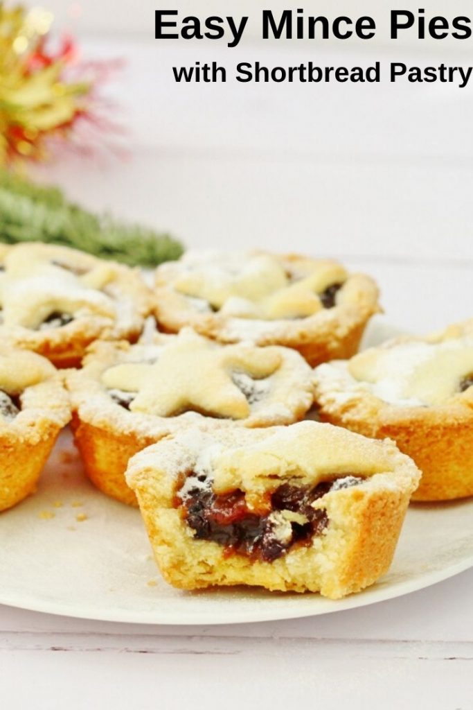 easy mince pies pin image with a plate of mince pies and one of the pies has been bitten in half