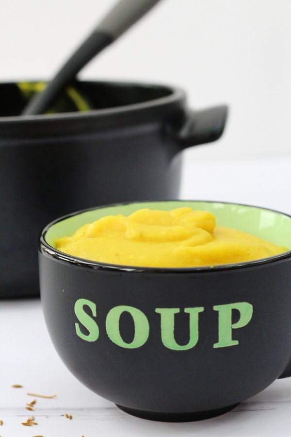 Roasted parsnip soup in a black and green soup bowl with the soup pot in the background