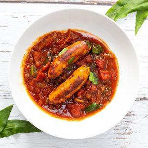 Sausage wild garlic stew in a white bowl