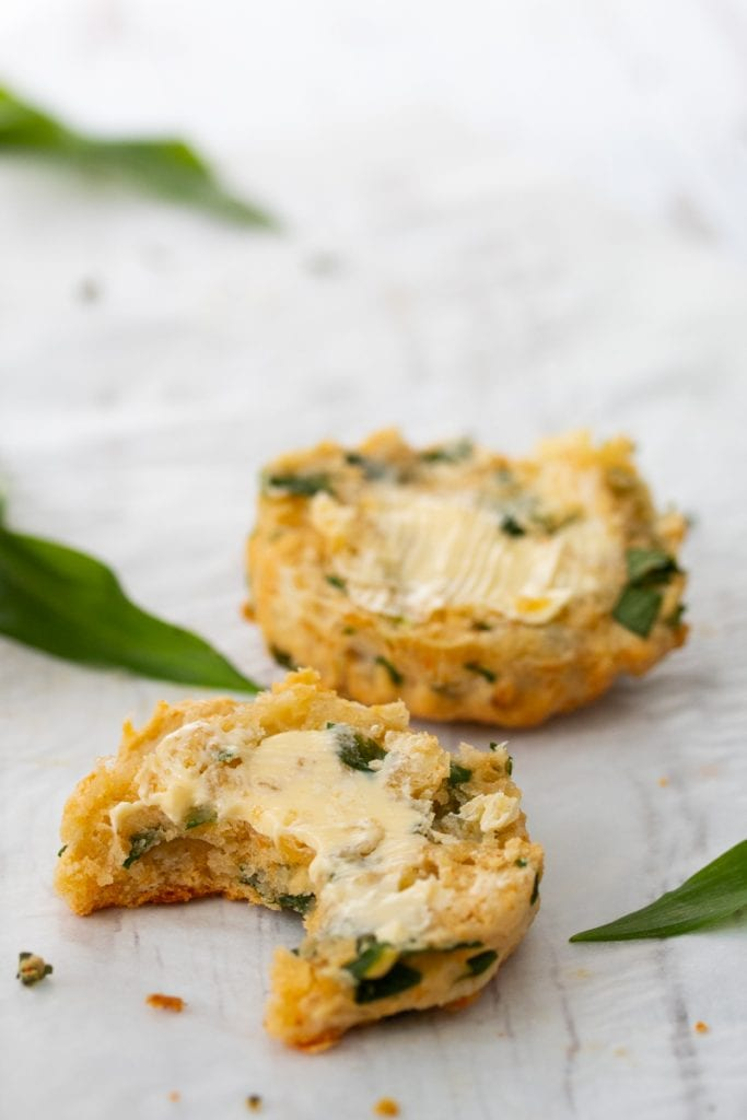 Cheesy wild garlic scone cut in half with butter on the top