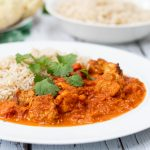 chicken tikka masala on a plate with rice