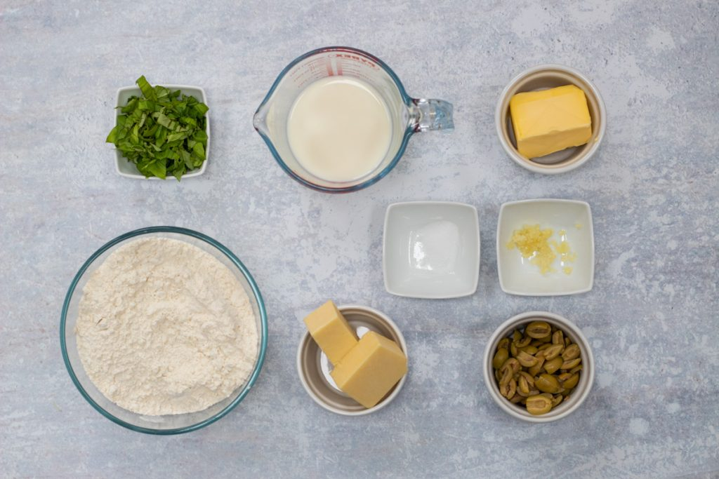 Ingredients for cheese and olive scones - self raising flour, butter, olives, mature cheddar cheese, butter, milk, garlic, salt, basil
