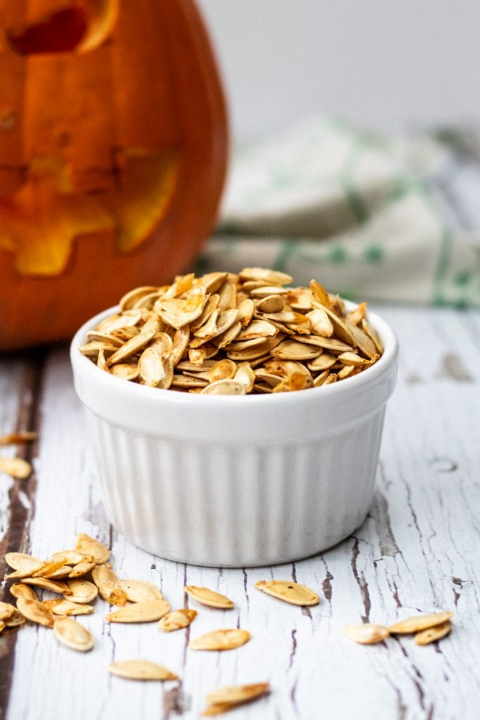roasted pumpkin seeds in a bowl with a pumpkin in the background