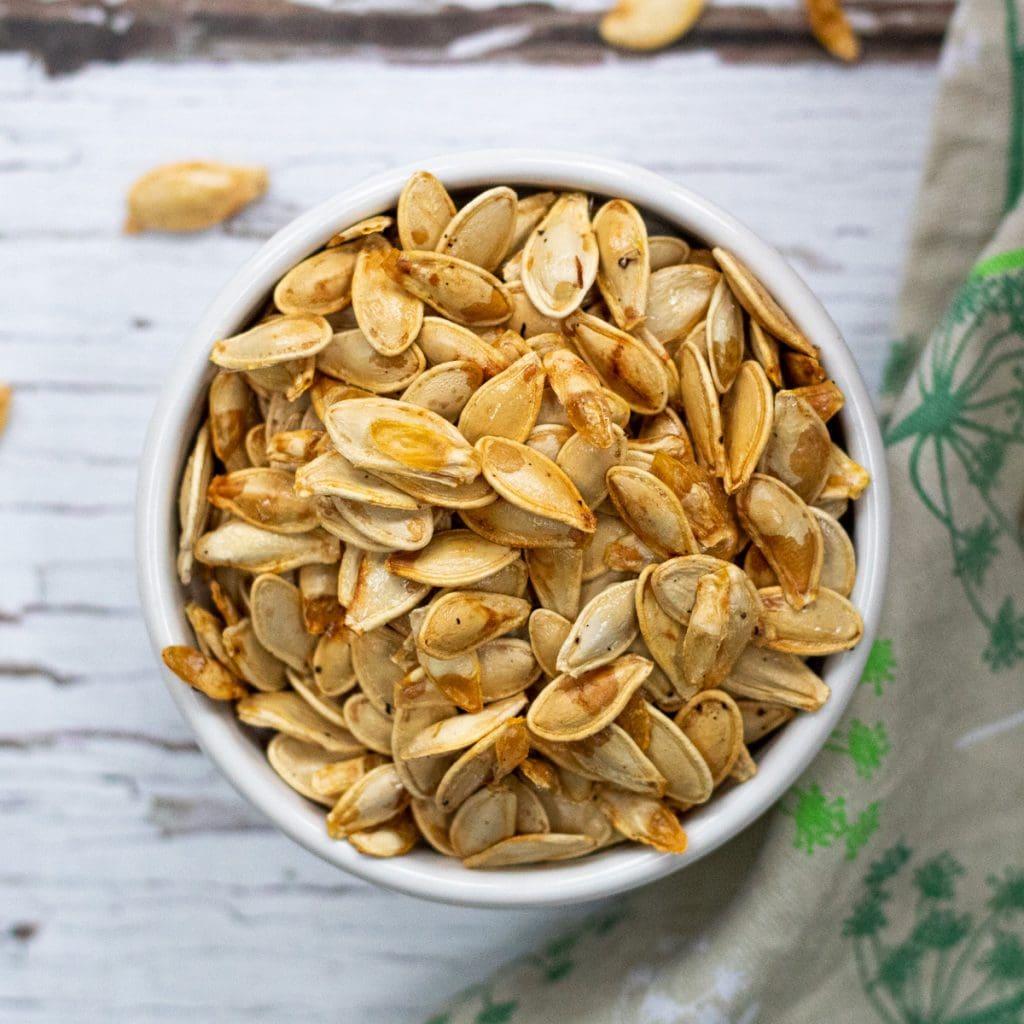 ramekin of roasted pumpkin seeds seasoned with salt and pepper