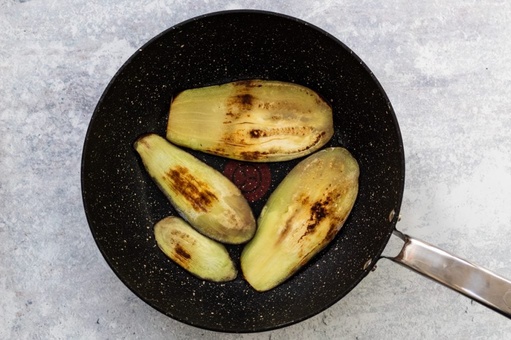Aubergine slices in a frying pan