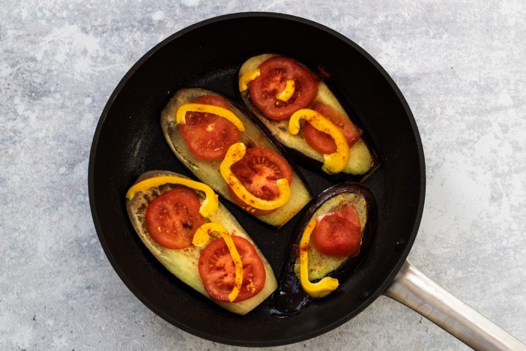aubergine slices, tomatoes and peppers in a frying pan