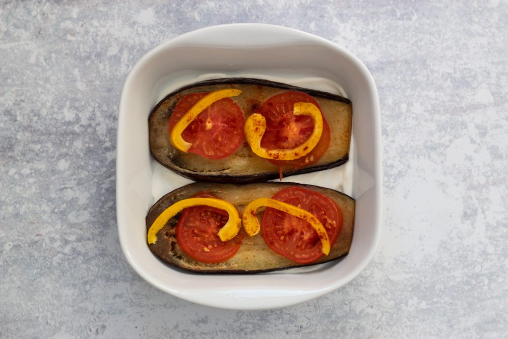 Assembling layers of aubergine, tomatoes, peppers and yogurt in a serving dish