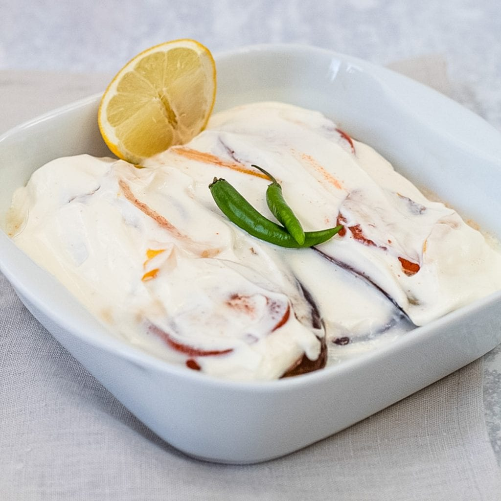 Serving dish with layers of aubergine in yogurt