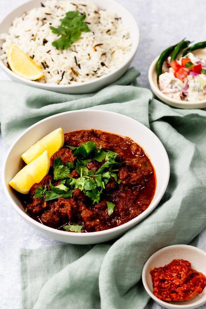 bowl of lamb vindaloo with rice and chutney